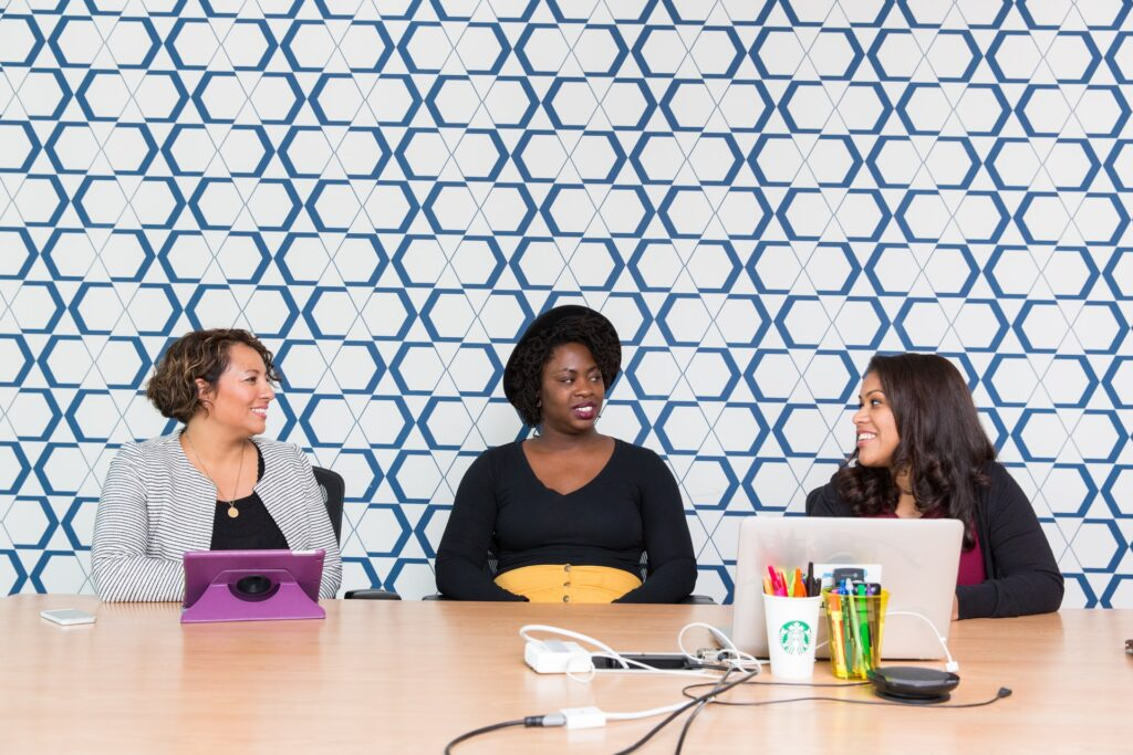three women sitting at a work desk talking with each other. Are they happy with their work? Do they have a great job match?