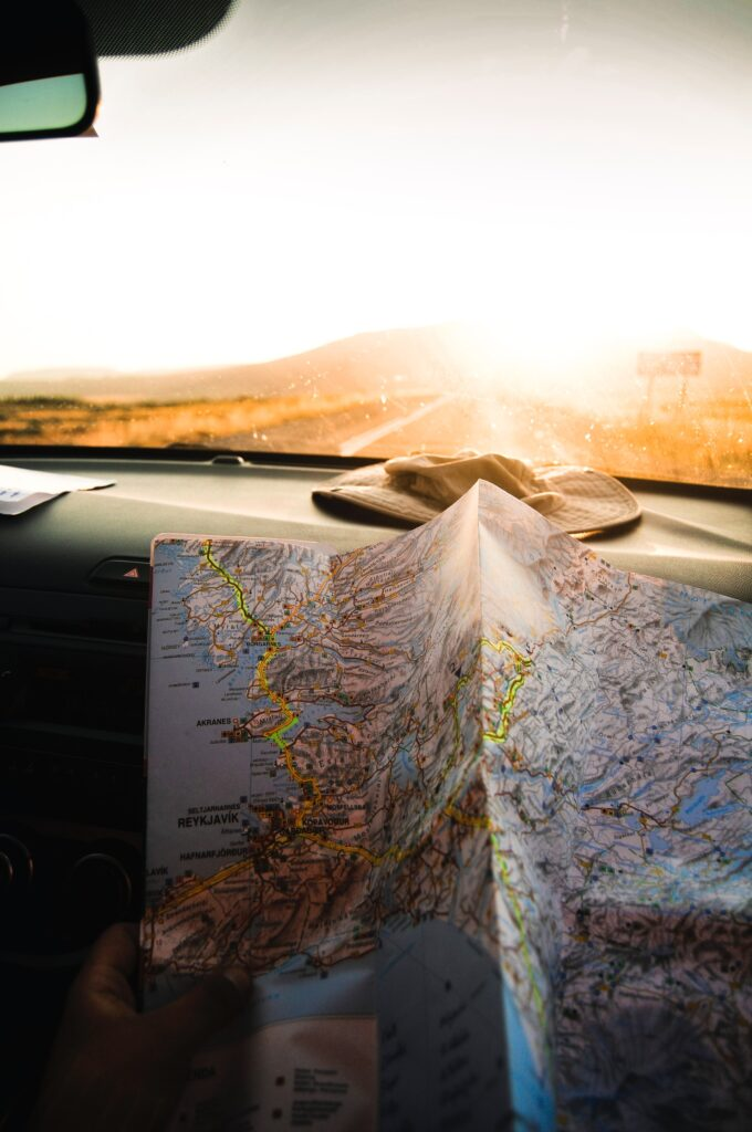A bright sun in the background with a car dashboard view and a map sitting on the dashboard. on the topic of home address on your resume