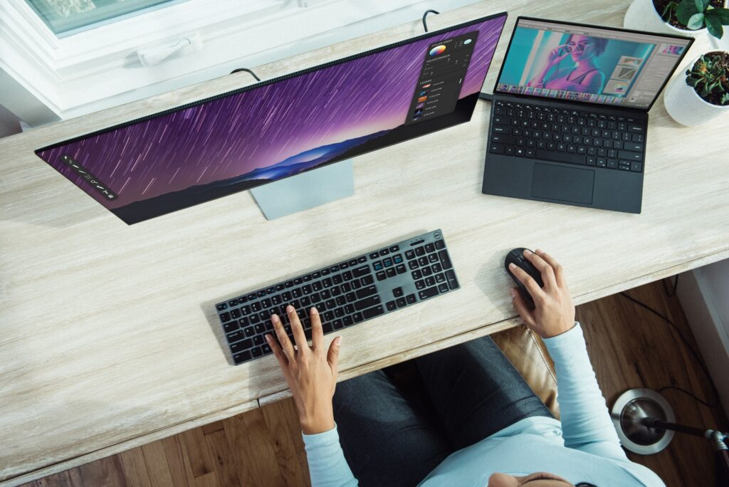 woman sitting at a desk in front of a desktop and laptop, conducting herself professionally while looking for work because of pandemic unemployment